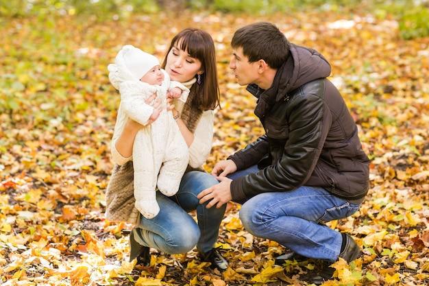 Lächelndes paar mit neugeborenem baby im herbstpark