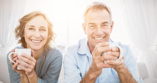 Lächelndes paar mittleren alters, das auf der couch sitzt und kaffee trinkt