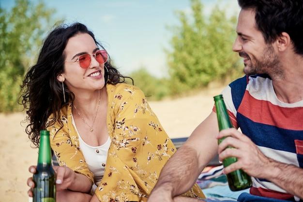 Lächelndes paar trinkt kaltes bier am strand