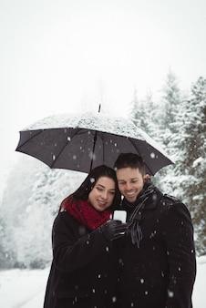 Lächelndes paar unter regenschirm, das handy im wald während des schneefalls benutzt