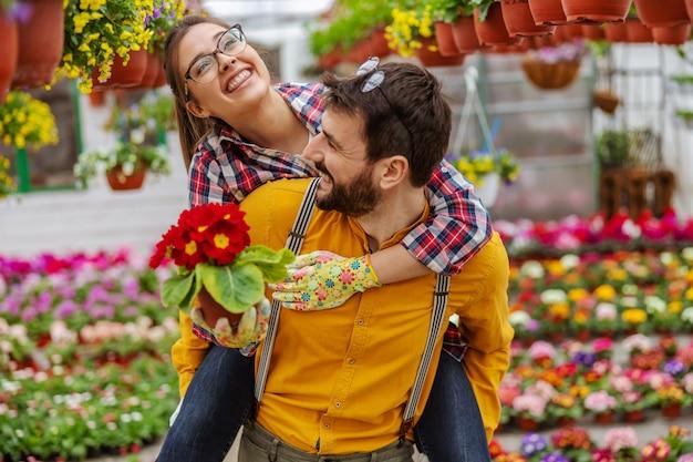 Lächelndes paar verliebt sich in huckepackfahrt im gewächshaus. überall um sie herum sind bunte blumen. frau, die blumen hält. kleinunternehmer.
