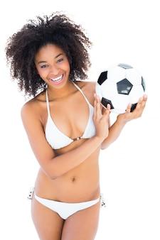 Lächelndes passendes mädchen im weißen bikini, der fußball hält