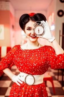 Lächelndes pin-up-mädchen posiert mit wecker, vintage-café-interieur, beliebte amerikanische mode 50er und 60er jahre. rotes kleid mit tupfen, helles make-up