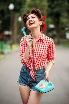 Lächelndes pinup-mädchen mit retro-drehtelefon, vintage amerikanische mode. sexy frau im pin-up-stil