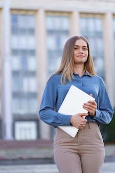 Lächelndes porträt der blonden jungen frau, die blaues sanftes hemd über gebäude trägt