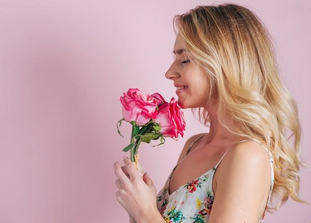 Lächelndes porträt der blonden jungen frau, die in der hand rosen gegen rosa hintergrund hält