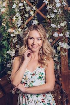 Lächelndes porträt der blonden jungen frau, die vor weißen blumen steht