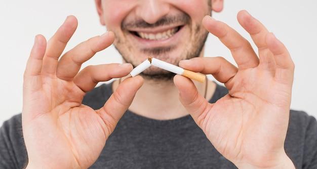Lächelndes porträt der hand eines mannes, die zigarette bricht