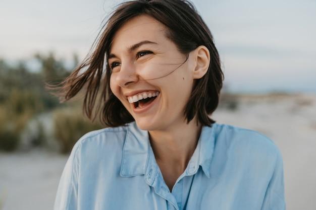 Lächelndes porträt der offenen lachenden frau am strand