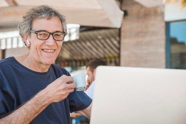 Lächelndes porträt des älteren mannes kaffeetasse caf c im freien halten