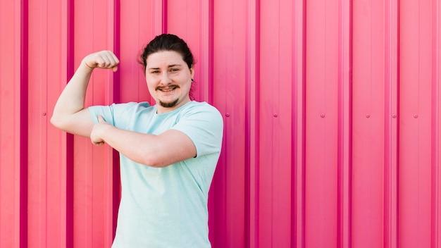 Lächelndes porträt des jungen mannes seinen muskel gegen rote gewölbte wand biegend