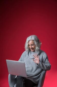 Lächelndes porträt einer älteren frau, die ihre hand während video plaudernd auf laptop wellenartig bewegt