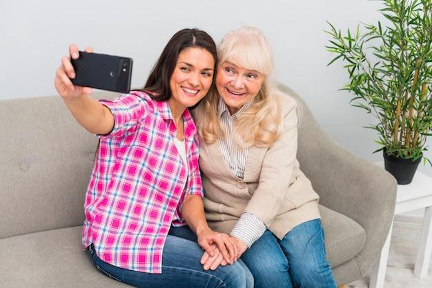 Lächelndes porträt einer älteren frau und der mutter, die selfie am handy nehmen