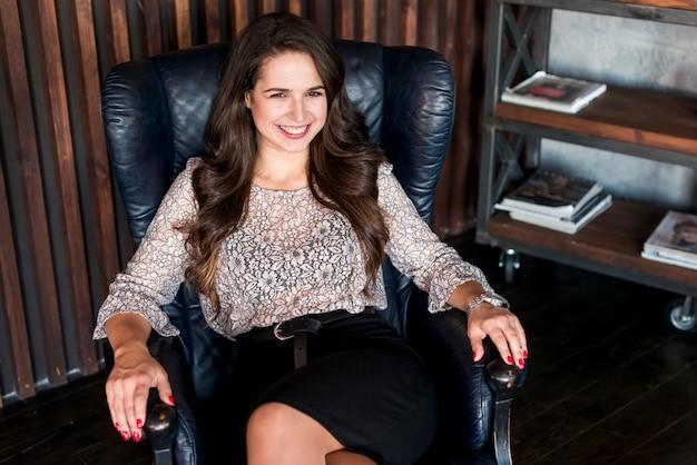 Lächelndes porträt einer attraktiven jungen frau, die auf lehnsessel sitzt