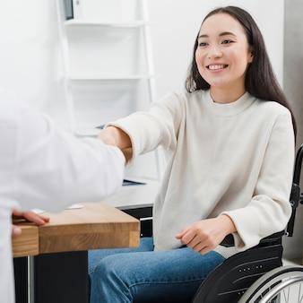 Lächelndes porträt einer behinderten jungen frau, die auf dem rollstuhl sitzt, der hände mit einer person am arbeitsplatz rüttelt