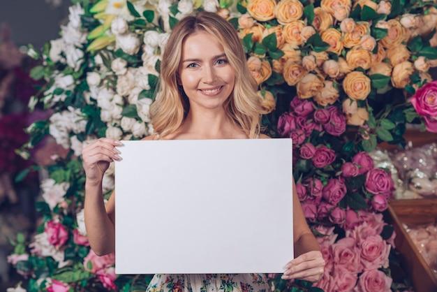 Lächelndes porträt einer blonden jungen frau, die leere weiße karte zeigt