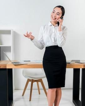 Lächelndes porträt einer geschäftsfrau, die vor dem schreibtisch spricht am handygestikulieren steht