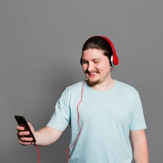 Lächelndes porträt einer hörenden musik des mannes am kopfhörer durch handy gegen graue wand