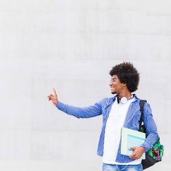 Lächelndes porträt einer jungen afroamerikanischen tragetasche des jungen mannes auf der schulter und büchern in der hand, die gegen wand stehen