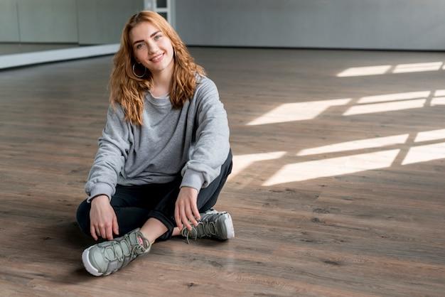 Lächelndes porträt einer jungen frau, die auf massivholzboden im tanzstudio sich entspannt