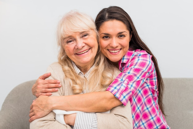 Lächelndes porträt einer jungen frau, die ihre ältere mutter umfasst