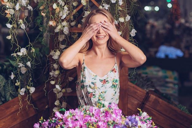 Lächelndes porträt einer jungen frau, die ihre augen mit zwei händen stehen vor blumen bedeckt