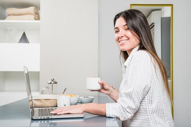 Lächelndes porträt einer jungen frau, die in der hand kaffeetasse unter verwendung des laptops hält