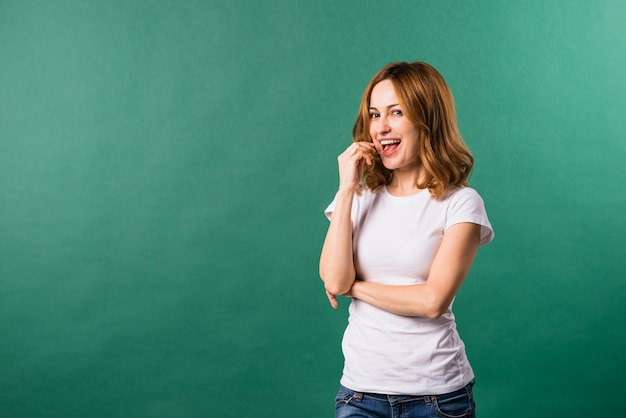 Lächelndes porträt einer jungen frau gegen grünen hintergrund