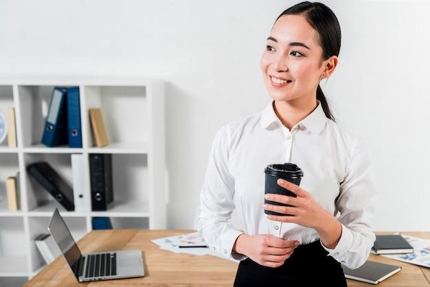 Lächelndes porträt einer jungen geschäftsfrau, die in der hand vor der tabelle hält wegwerfkaffeetasse steht