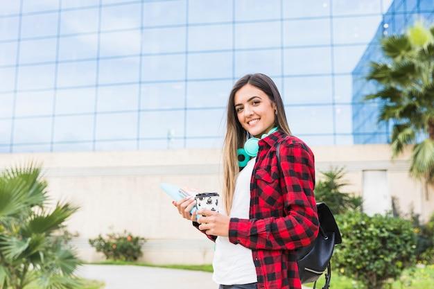 Lächelndes porträt einer jungen studentin, welche die bücher und mitnehmerkaffeetasse stehen vor universitätsgebäude hält