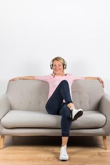 Lächelndes porträt einer reifen frau, die auf hörender musik des grauen sofas auf kopfhörer sitzt