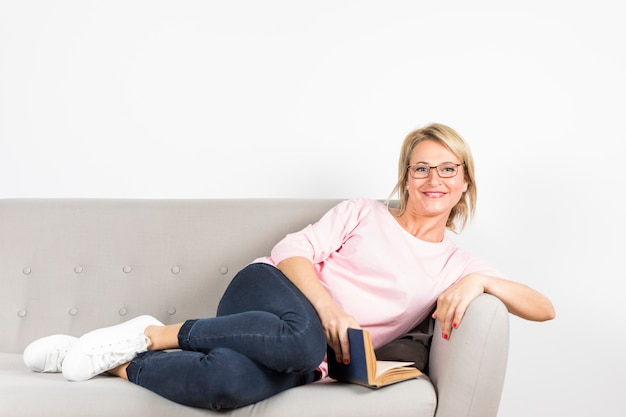 Lächelndes porträt einer reifen frau, die sich in der hand auf grauem sofa mit dem buch betrachtet kamera lehnt