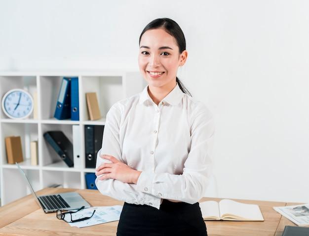 Lächelndes porträt einer überzeugten jungen geschäftsfrau, die vor der tabelle schaut zur kamera steht