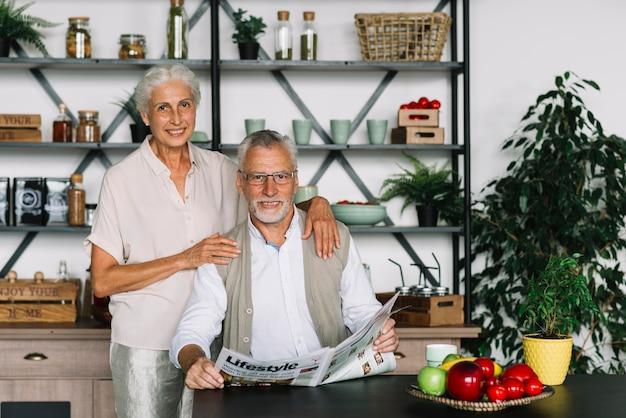 Lächelndes porträt eines älteren mannes, der in der küche sitzt