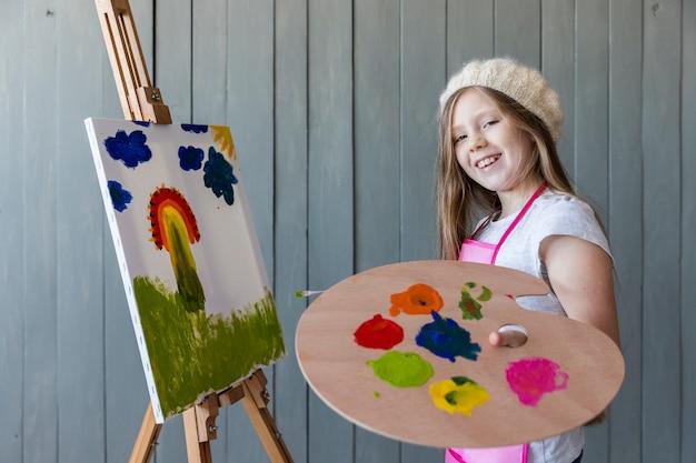 Lächelndes porträt eines blonden mädchens, das in der hand die hölzerne palette malt das segeltuch hält