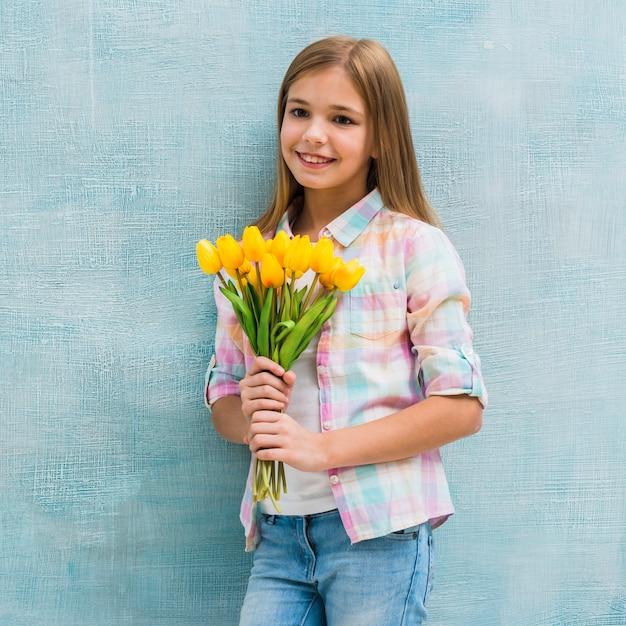 Lächelndes porträt eines blonden mädchens, welches in der hand die tulpen schaut zur kamera hält