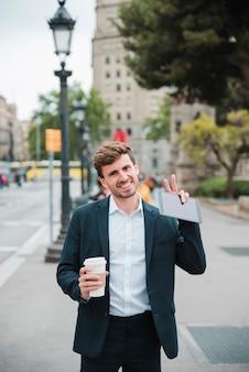 Lächelndes porträt eines geschäftsmannes, der mitnehmerkaffeetasse und die digitale tablette zeigt siegesgeste hält
