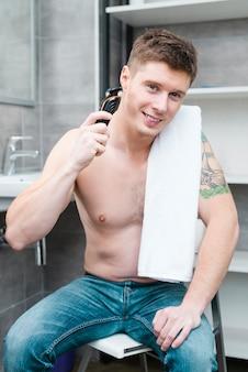 Lächelndes porträt eines hemdlosen jungen mannes, der im badezimmer rasiert mit elektrorasierer sitzt