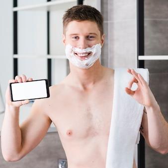 Lächelndes porträt eines hemdlosen jungen mannes mit tuch auf seiner schulter, die in der hand das intelligente telefon zeigt okayzeichen hält
