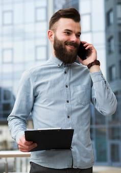 Lächelndes porträt eines hübschen jungen mannes, der in der hand das klemmbrett spricht am handy hält