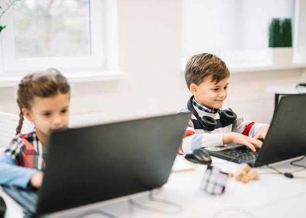 Lächelndes porträt eines jungen, der den laptop sitzt mit einem mädchen im klassenzimmer verwendet