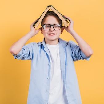 Lächelndes porträt eines jungen, der ein offenes buch auf seinem kopf steht gegen gelben hintergrund hält