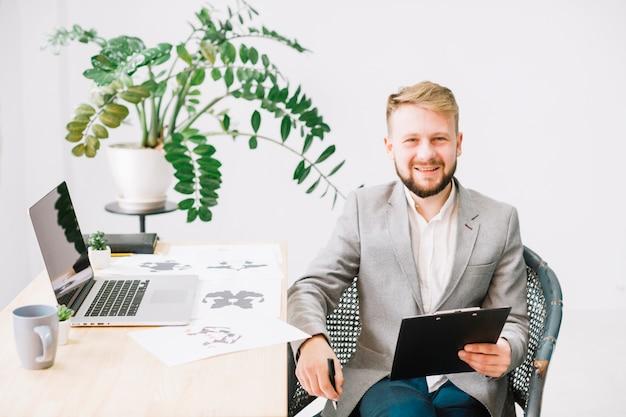 Lächelndes porträt eines jungen männlichen psychologen, der am arbeitsplatz mit laptop und rorschach inkblot testpapier sitzt