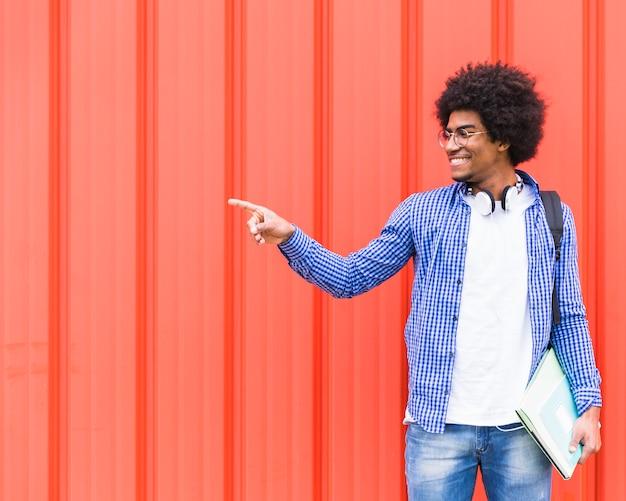 Lächelndes porträt eines jungen männlichen studenten, der finger auf etwas zeigt, das gegen rote wand steht