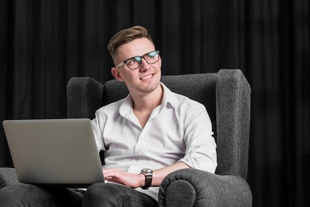 Lächelndes porträt eines jungen mannes, der auf lehnsessel unter verwendung der digitalen tablette sitzt, die weg schaut