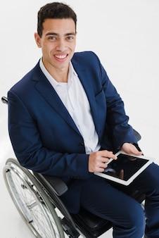 Lächelndes porträt eines jungen mannes, der auf rollstuhl unter verwendung der digitalen tablette sitzt