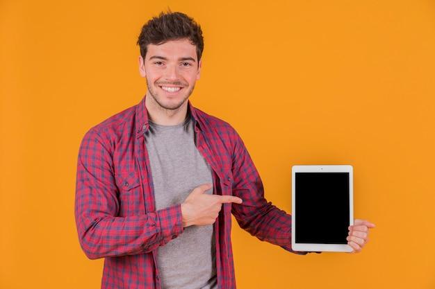 Lächelndes porträt eines jungen mannes, der etwas auf digitaler tablette gegen einen orange hintergrund zeigt