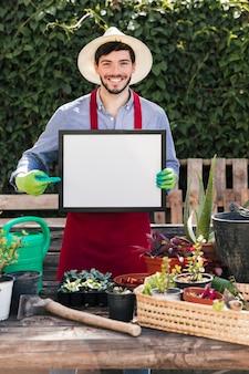 Lächelndes porträt eines jungen mannes, der hinter den topfpflanzen zeigen den finger auf weißem leerem rahmen steht