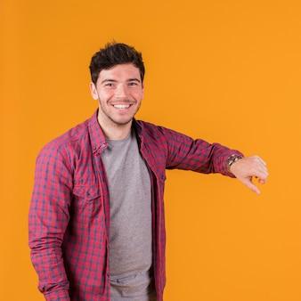 Lächelndes porträt eines jungen mannes, der zeit auf seiner armbanduhr zeigt