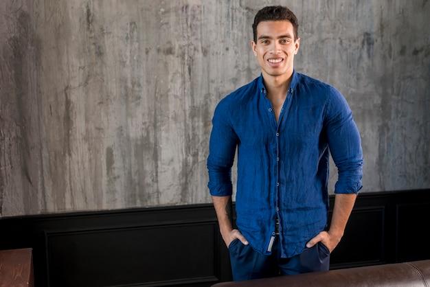 Lächelndes porträt eines jungen mannes mit seinen händen in der tasche